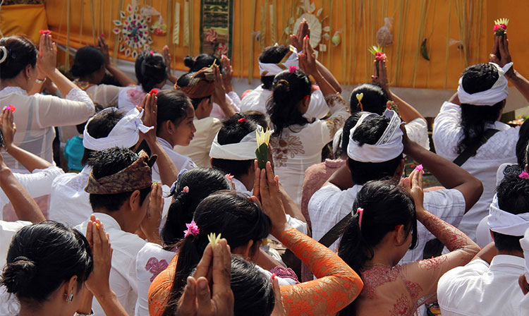 Spirituality in Bali part of the yoga teacher training experience. Balinese people praying in the temple