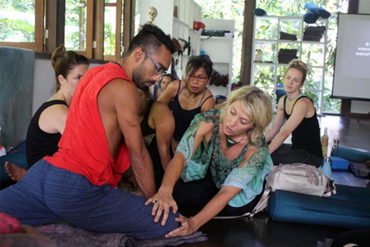 Functional Anatomy teacher Rachel Ellery adjusting a student in pigeon pose