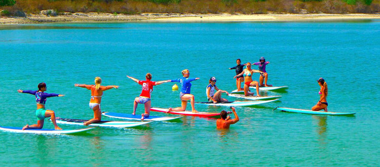 SUP Yoga in Sanur. Practicing yoga on paddle boards in the ocean in Bali